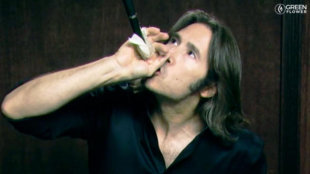man smoking a chillum with one hand